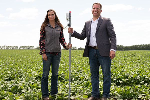 Stuart Cullum, President of Olds College and Catalina Oitzl, current Olds College Student plant a soil and crop evaluation sensor into the 孩子大学JDB电子游戏