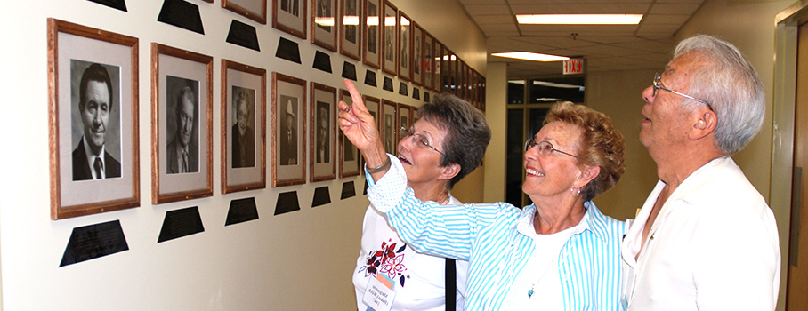 Alumni look at the Hall of Fame and Merit wall